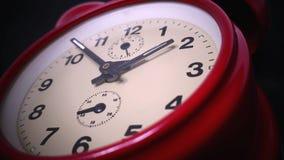 Cantidad de un reloj rojo viejo aislado en un fondo negro almacen de metraje de vídeo