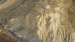 Cantidad del abejón del campista femenino aventurero en un borde del acantilado en bahía hermosa del zorro en Crimea Tiro aéreo a almacen de metraje de vídeo