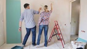 Cantidad del baile de los pares y de la diversión jovenes divertidos el tener mientras que pinta las paredes y hace la renovación