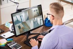 Cantidad del CCTV de Looking At del hombre de negocios en el ordenador fotos de archivo