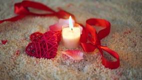 Cantidad del día de San Valentín, de la cinta y de la vela de la decoración quemando en la arena