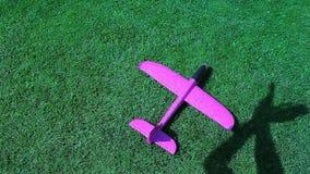 Cantidad del hd del fondo de la sombra de la mano de hierba verde del aeroplano del juguete metrajes