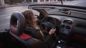 Cantidad del hombro - mujer de pelo largo joven que conduce el coche convertible a lo largo de la ciudad, disfrutando del verano  almacen de metraje de vídeo