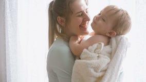 Cantidad del primer de la cámara lenta de la madre sonriente feliz que abraza a su hijo del bebé en la ventana en dormitorio almacen de metraje de vídeo
