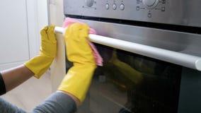 Cantidad del primer 4k de la mujer joven en los guantes de goma amarillos que limpian la manija eléctrica del horno metrajes
