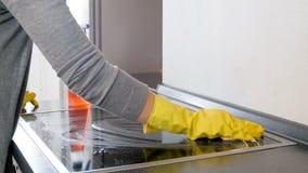 Cantidad del primer 4k de la mujer joven que rocía la estufa eléctrica detergente y que se lava en cocina con la esponja almacen de metraje de vídeo