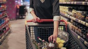 Cantidad del traje femenino que escoge productos en un colmado y que los pone al carro del empuje que hace compras mientras que c metrajes