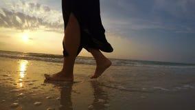 cantidad en tiempo real 4K de una mujer que camina a lo largo de la playa en la puesta del sol almacen de video