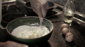 Cantidad en tiempo real silenciada de los huevos de mezcla de un cocinero con la harina en un cuenco para hacer la pasta almacen de video