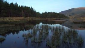 Cantidad hermosa del lago inmóvil y montañas contra el cielo metrajes