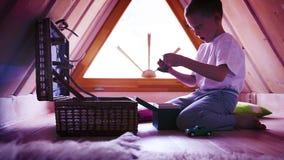 Cantidad intensivo púrpura-entonada: un niño pequeño que retira los juguetes de un pecho en su sitio del ático almacen de video
