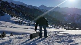 cantidad 4k de la aventura acertada del hombre del snowboarder a la montaña del invierno almacen de video