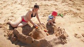 cantidad 4k de la madre joven en castillo de la arena del edificio del bikini en la playa del mar con sus 3 a?os del hijo metrajes