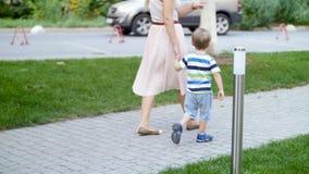 cantidad 4k de la madre joven que detiene a su hijo del niño a mano y que camina en la trayectoria en el parque metrajes