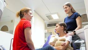 cantidad 4k de la madre joven que habla con el dentista sobre el tratamiento de los dientes de su hija almacen de video