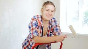 cantidad 4k de la mujer sonriente feliz que presenta con el rodillo de pintura en el nuevo apartamento almacen de metraje de vídeo