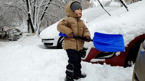 cantidad 4k de poco coche que asierra del niño pequeño pegado en nieve acumulada por la ventisca después de tormenta de la nieve  almacen de metraje de vídeo