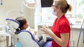 cantidad 4k del dentista que sacude la mano del ` s de la muchacha después del tratamiento de los dientes almacen de metraje de vídeo