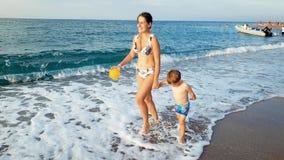 cantidad 4k del niño pequeño alegre que celebra a su madre a mano y que camina en la playa metrajes