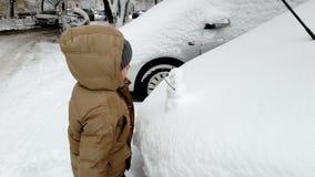 cantidad 4k del niño pequeño que mira el pequeño muñeco de nieve en la capilla del coche metrajes
