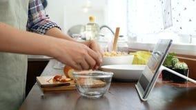 cantidad 4k la tableta de la diapositiva de la mano y el huevo femeninos de la grieta adentro al bol de vidrio preparar los ingre almacen de video