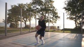 Cantidad lateral de un jugador de básquet de la chica joven que entrena y que ejercita al aire libre en la corte local Goteo con almacen de metraje de vídeo