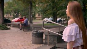 Cantidad móvil de la mujer joven del jengibre que camina arriba y que sonríe, hembra que va adelante con los hombros desnudos metrajes