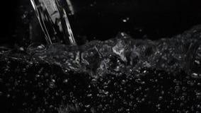 Cantidad macra del agua que vierte en un envase transparente Fondo negro Tiro de la macro del primer metrajes