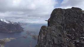 Cantidad a?rea del caminante masculino en el top de la monta?a que pasa por alto paisaje hermoso de las islas de Lofoten en esc?n almacen de video