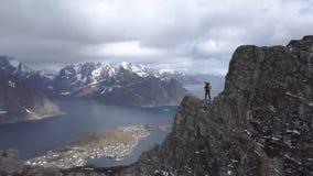 Cantidad a?rea del caminante masculino en el top de la monta?a que pasa por alto paisaje hermoso de las islas de Lofoten en esc?n almacen de metraje de vídeo