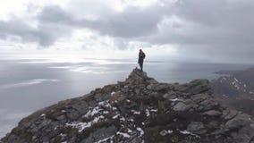 Cantidad a?rea del caminante masculino en el top de la monta?a que pasa por alto paisaje hermoso de las islas de Lofoten en esc?n metrajes