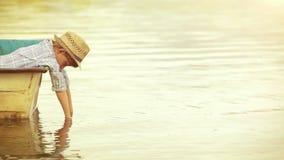 Cantidad soleada: un muchacho se sienta en un barco, inclinándose sobre el a bordo y poniendo sus manos en el agua metrajes
