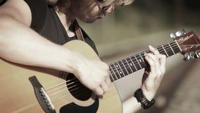 Cantidad triste de un guitarrista de pelo largo que juega una canción en acordes simples metrajes