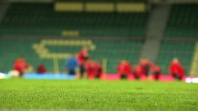 Cantidad Unfocused del fondo de los jugadores del fútbol (fútbol) que calientan en el día del partido almacen de metraje de vídeo