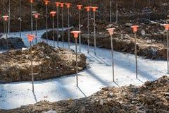 Cantiere con il tondo per cemento armato nei basamenti versati per una costruzione fotografia stock libera da diritti
