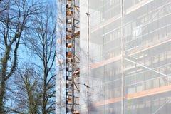 Cantiere con l'armatura sulla facciata di costruzione a più piani durante il rinnovamento fotografie stock libere da diritti