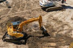 Cantiere con la terra di scavatura dell'escavatore Fotografia Stock