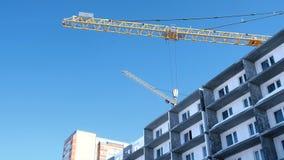 Cantiere con le gru sul fondo del cielo Il costruttore lavora al tetto di una costruzione multipiana archivi video