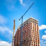 Cantiere con le gru vicino alla costruzione contro il cielo blu con le nuvole bianche immagini stock