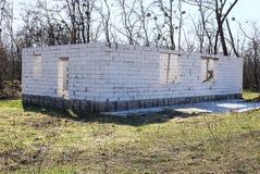 Cantiere con una casa con mattoni a vista grigia non finita in erba verde fotografie stock