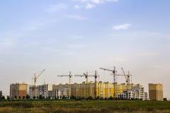 Cantiere di alta costruzione del nuovo appartamento con le gru a torre contro cielo blu Sviluppo di zona residenziale Bene immobi Fotografie Stock