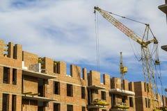 Cantiere di alta costruzione del nuovo appartamento con le gru a torre contro cielo blu Sviluppo di zona residenziale Bene immobi Fotografia Stock