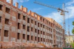 Cantiere di alta costruzione del nuovo appartamento con le gru a torre contro cielo blu Sviluppo di zona residenziale Bene immobi Immagine Stock