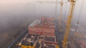Cantiere nella nebbia con un occhio del ` s dell'uccello con le gru a torre sul tramonto archivi video