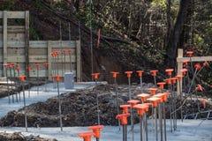 Cantiere sul pendio di collina con i basamenti versati e sul tondo per cemento armato con i cappucci di sicurezza arancio fotografia stock