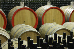 Cantina con i barilotti di legno e le bottiglie di vetro riempite 7 Fotografia Stock