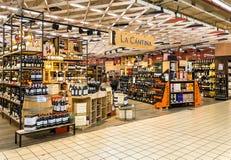 Cantina do La da loja de vinho com uma exposição larga de garrafas de vinho para dentro do IPER do hipermercado de Varese, interi imagens de stock