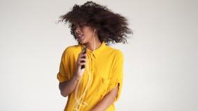 Canto afroamericano della donna mentre musica d'ascolto sul app del telefono cellulare stock footage