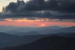 Canto ahumado de las montañas en la puesta del sol nublada Foto de archivo