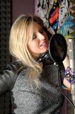 Canto attraente della donna nello studio di registrazione Immagine Stock